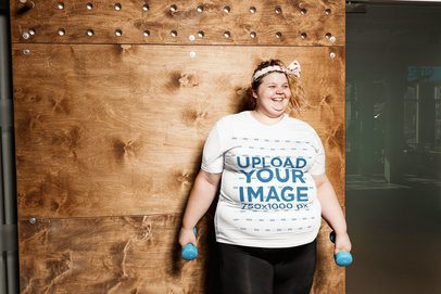 Mockup of a Woman with a Plus Size T-Shirt Holding Two Dumbbells 34623-r-el2