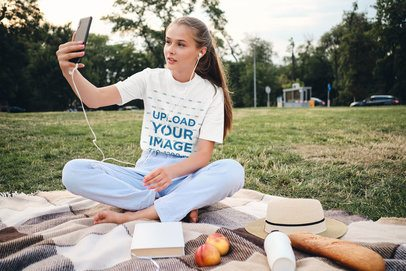 Tee Mockup of a Woman Doing a Video Call at an Outdoor Picnic 34472-r-el2