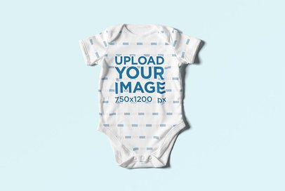 Mockup of a Baby Onesie Lying Flat on a Colored Surface 4584-el1