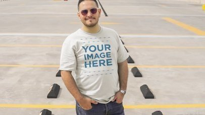 Tee Video Mockup of a Young Plus Size Man Styling a T-Shirt with Sunglasses in a Parking Lot a12463-122016