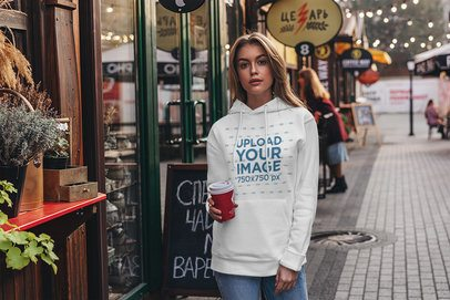 Mockup of a Woman Wearing a Customizable Hoodie and Holding a Coffee 4780-el1