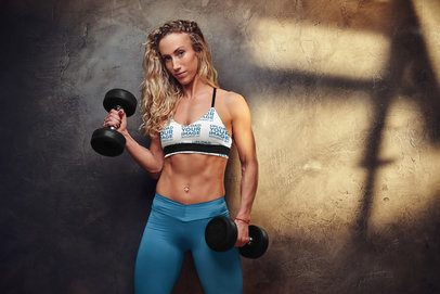 Sports Bra Mockup of a Woman Posing With Two Dumbbells Against a Concrete Wall 38566-r-el2