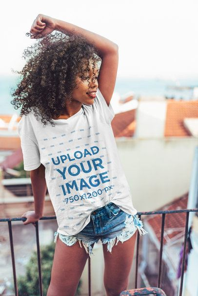 Mockup of a Curly-Haired Woman Wearing an Oversized T-Shirt on a Balcony 34951-r-el2
