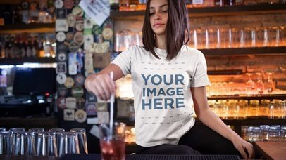 Trendy Girl Stirring a Drink at a Bar T-Shirt Mockup Cinemagraph a13400