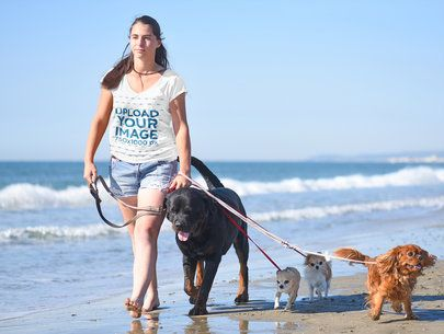 Mockup of a Woman with a V-Neck Tee Walking on the Beach with Her Dogs 39066-r-el2