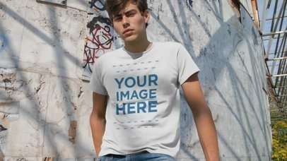 Young Man Using Round Neck Tee Relaxing at Abandoned Place Grafitti Mockup Video a13751