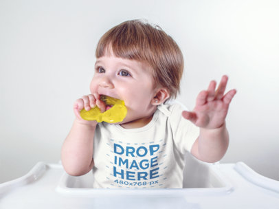 Baby Girl Wearing A Onesie While Biting Her Toy Sitting Down Mockup a13960