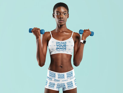 Sports Bra Mockup of a Woman Wearing Bike Shorts and Holding Two Dumbbells 41176-r-el2