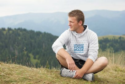 Mockup of a Man Wearing a Hoodie Featuring Mountains in the Background 40139-r-el2