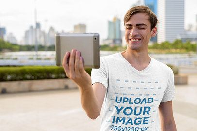 Mockup of a Man with a Heather V-Neck Tee Taking a Selfie 40296-r-el2