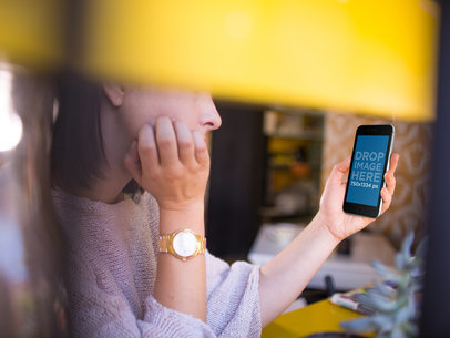 Young Woman Holding Her iPhone While At A Coffee Shop Mockup a14003