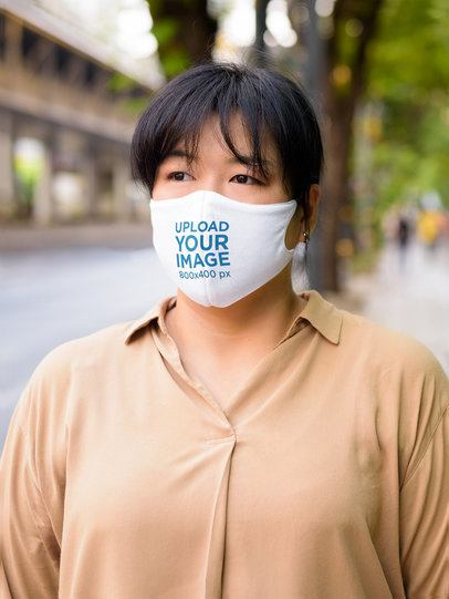 Mockup of a Serious Woman Standing on the Street Wearing a Face Mask 41627-r-el2