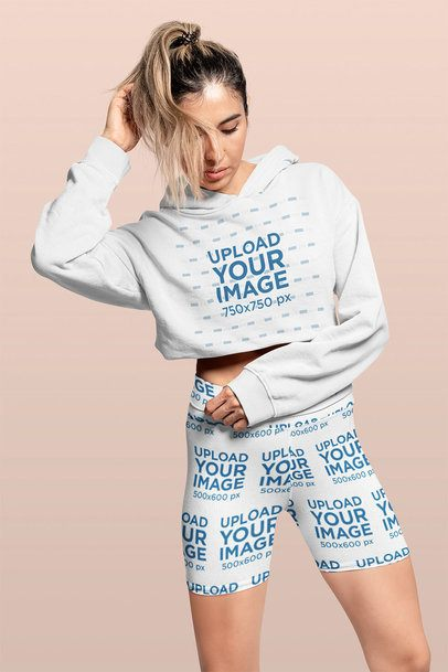 Crop Top Hoodie and Bike Shorts Mockup Featuring a Woman Posing in a Studio 42356