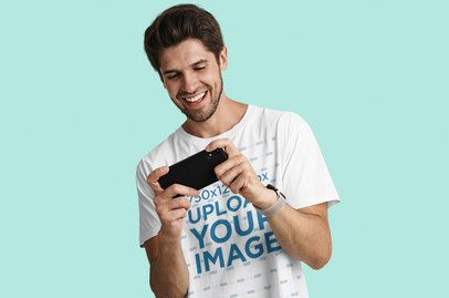 T-Shirt Mockup Featuring a Playing Games on His Phone 42847-r-el2