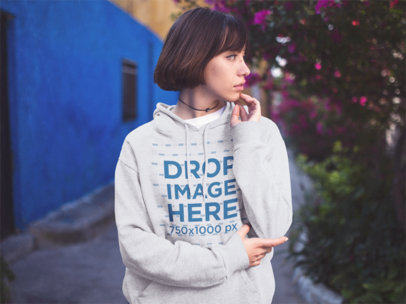 Young Trendy Girl Looking Away While Wearing a Pullover Hoodie in the Street Mockup a12679