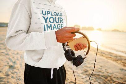Hoodie Mockup of a Man Carrying Headphones at the Beach 43516-r-el2