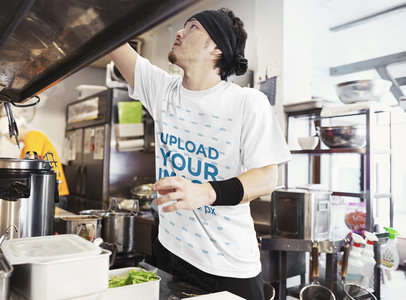 T-Shirt Mockup Featuring a Man in a Restaurant's Kitchen 43045-r-el2