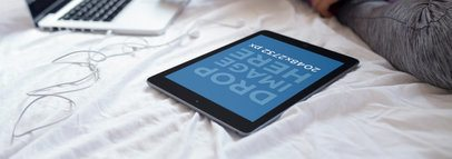 Mockup of an iPad in Portrait Position Laid on a Bed Next to a Laptop 14262awide