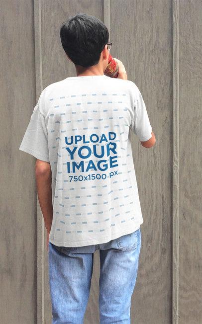 T-Shirt Mockup of a Young Man Staring at a Wooden Wall 45588-r-el2