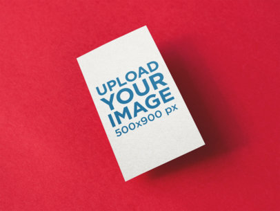 Vertical Business Card Mockup Floating Over a Red Surface a14991