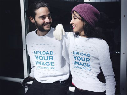 Happy Young Couple Wearing Different Crewneck Sweatshirts While at an Ice Skating Park a15480