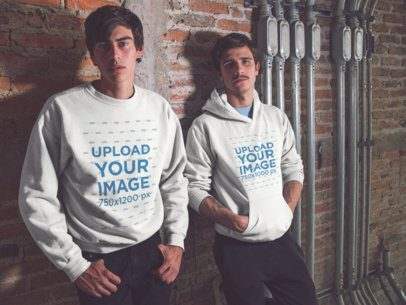 Two White Guys Wearing Different Designs on a Crewneck Sweatshirt and a Pullover Hoodie Template Whlie Lying Against a Bricks Wall a15584