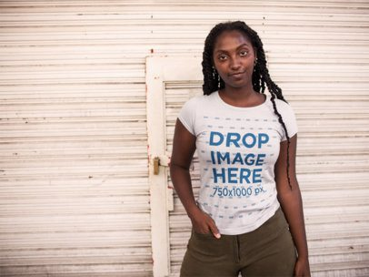 Young Black Girl Wearing a Round Neck Tshirt Mockup While Standing Against a White Urban Background a15537