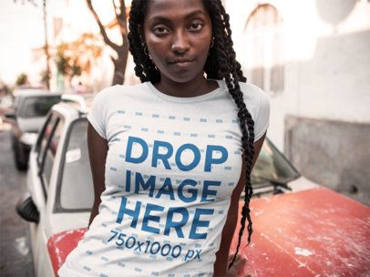 Closeup Mockup of a Serious Black Girl Wearing a Round Neck Tee While Lying Against a Car a15560