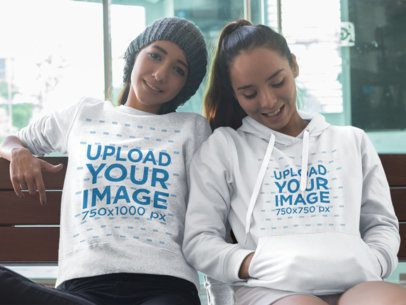Two Young Girls Sitting Down Together Wearing a Crewneck Sweatshirt and a Pullover Hoodie Mockup with Different Designs a15780