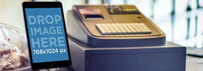 Mockup of an iPad Mini Next to a Cashing Machine