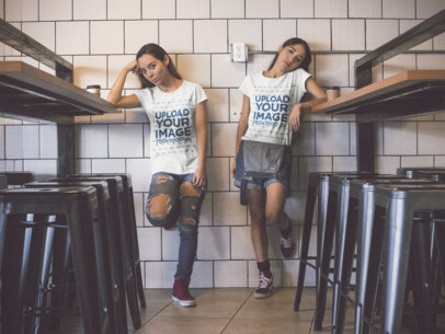 Pair of Girls Wearing Round Neck Tees Mockup while Standing Bored Against a White Tiles Wall a15796