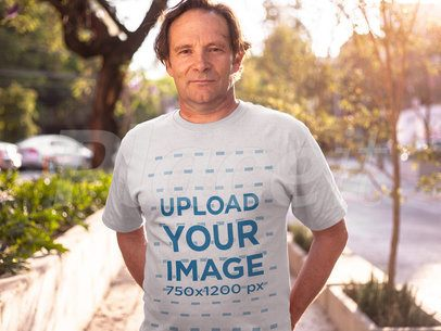 Middle Aged Man Wearing a Round Neck Tshirt Mockup While Standing Against the Sun a15931