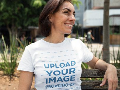 Smiling Middle Aged Woman Wearing a T-Shirt Template While Sitting on a Bench a15873