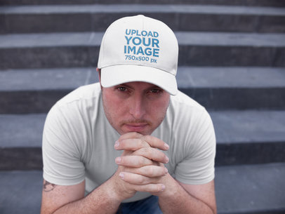 White Guy Sitting Down on Concrete Stairs While Wearing a Dad Hat Mockup a15881