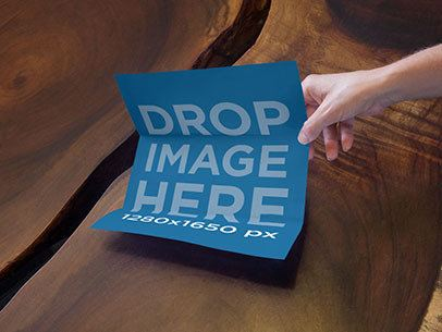 Mockup of a Person Grabbing a Brochure From a Wooden Coffee Table a6331