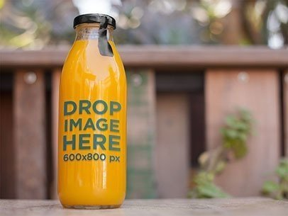 Label Mockup of a Juice Bottle Sitting on Top of a Table at a Patio a7023