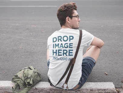 Tee Mockup Featuring a Young Hipster Man Sitting on a Sidewalk a11529