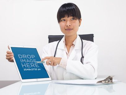 Doctor Pointing at Her iPad Pro in Her Office Mockup a12306