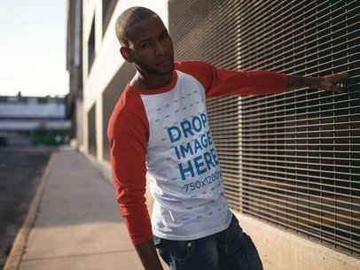 Young Black Man Wearing a Raglan T-Shirt Mockup Holding On to a Fence a12558