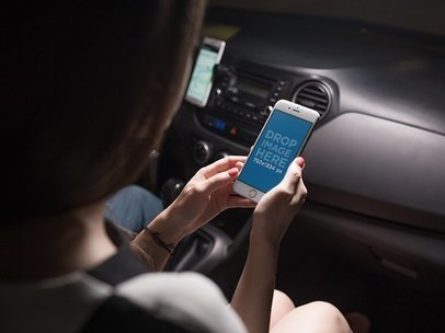 Mockup of a Woman Looking at an iPhone in Portrait Position in a Car 12801