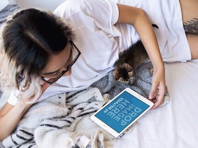 Young Woman in Bed with her Cat Using her iPad Mini Mockup a12813