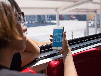 Mockup of a Woman Holding an iPhone in Portrait Position During a Bus Ride 12938s