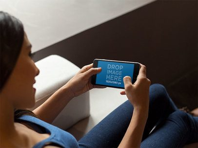 iPhone Mockup in Landscape Position of a Woman Sitting on a Modern Couch 13104s