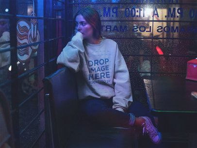 Young Woman with a Crewneck Sweatshirt Mockup Staring Out the Window a12686