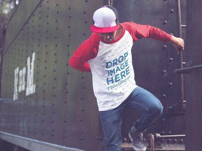 Guy Wearing a Cap and Raglan 3/4 Sleeve T-Shirt Mockup Jumping from a Train a12492