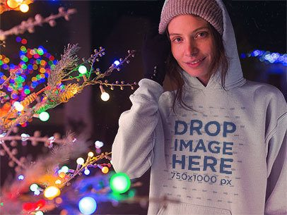 Hoodie Mockup Featuring a Lovely Girl Wearing a Beanie Near Christmas Lights a13246