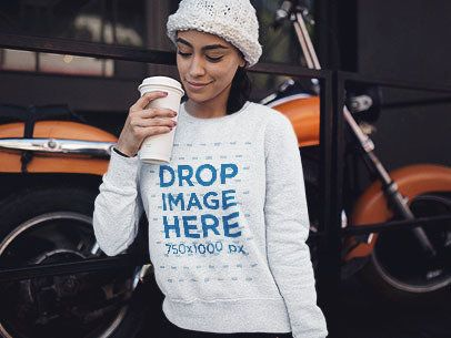 Young Woman with a Beanie and Heather Crewneck Mockup Having a Coffee in the Cold Against a Motorcycle a13173