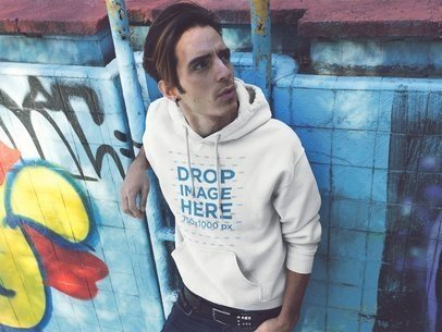 Pullover Hoodie Mockup Featuring a Trendy Guy Against a Graffiti Wall in the Street a12841