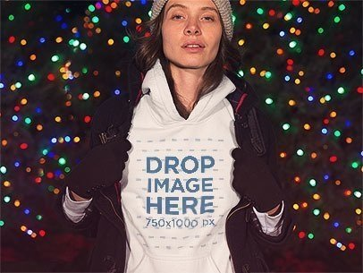 Lovely Woman Wearing a Hoodie Mockup with a Jacket in Front of Christmas Lights a13245