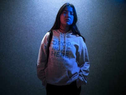 Hoodie Mockup of a Trendy Asian Girl with Long Hair Standing in a Blue Light a12717